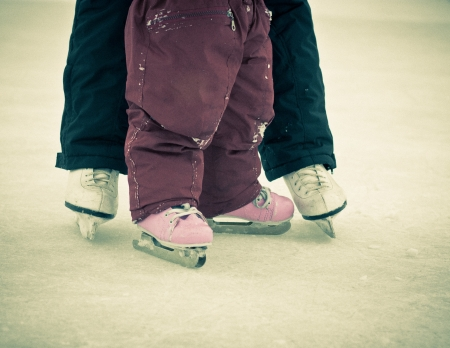 Child and parent feet on skates on ice in a retro style. photo