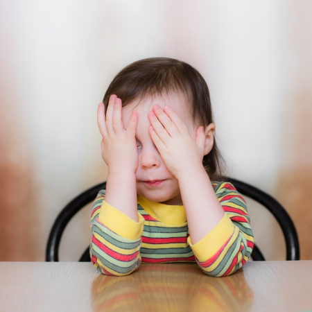 Frightened child closed his hands over eyes. photo