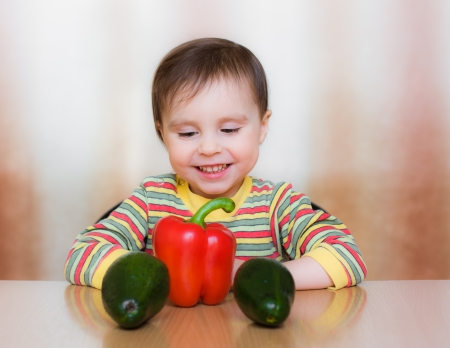Happy Kid with vegetables sitting at the table. Stock Photo - 23784032