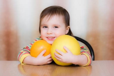 Happy Kid with pomelo sitting at the table. Stock Photo - 23784053
