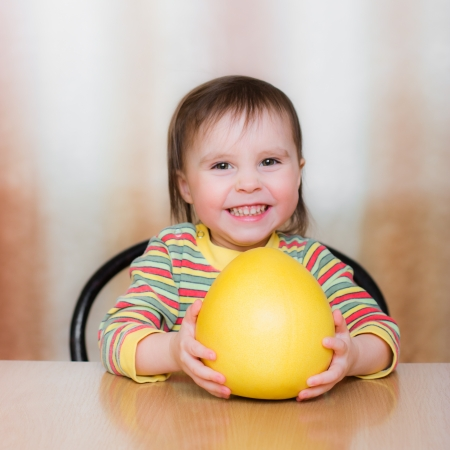 Happy Kid with pomelo sitting at the table. Stock Photo - 23784056