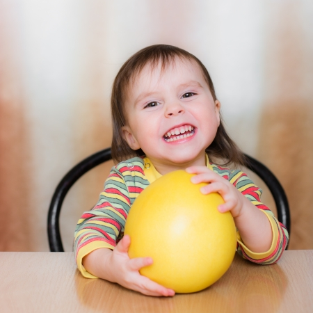 Happy Kid with pomelo sitting at the table. Stock Photo - 23784057