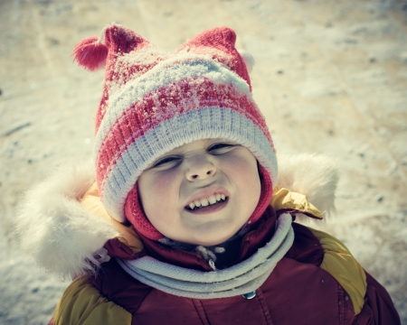 wearied: The sad child outside in the winter.