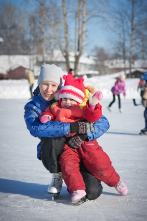 Mother with baby skates on ice skating in the winter Stock Photo - 23737756