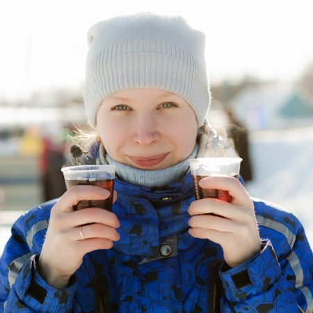 Woman holding hot drink outside in the winter  photo