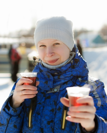 Woman holding hot drink outside in the winter. photo