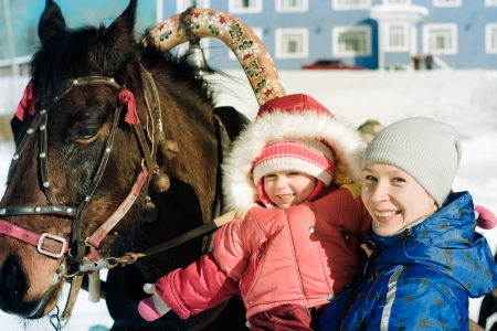harnessing: Mom, child and horse in the winter outdoors.