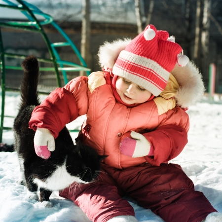 Funny happy child playing with cat outdoors in winter. photo