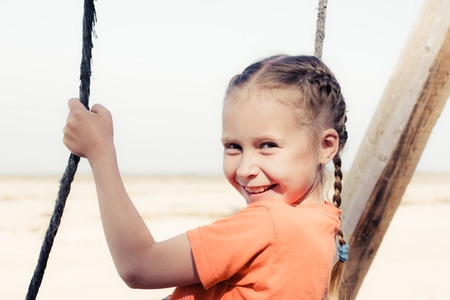 Little girl on the beach on a swing close up portrait. photo