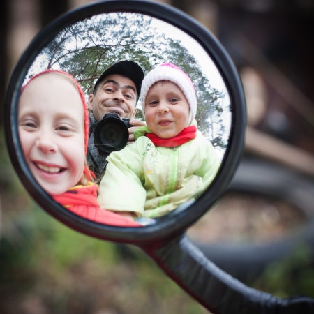 Father with children looking at the a distorting mirror  photo