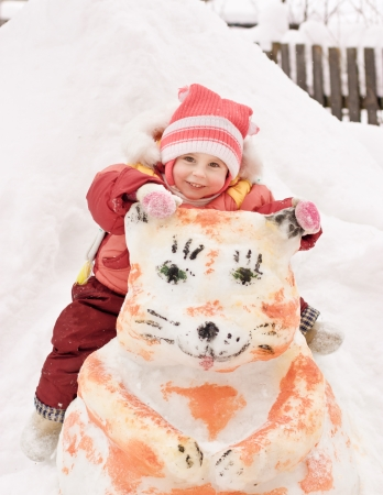 Happy baby sitting on a snowman in winter  photo