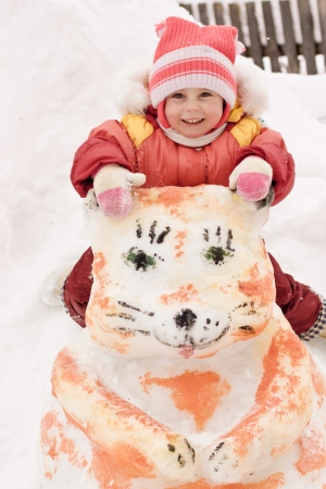 Happy baby sitting on a snowman in winter. photo