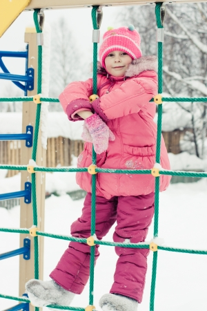 Beautiful happy kid in the red jacket in the winter outdoors. photo