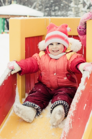 Beautiful happy kid in the red jacket in the winter outdoors  photo