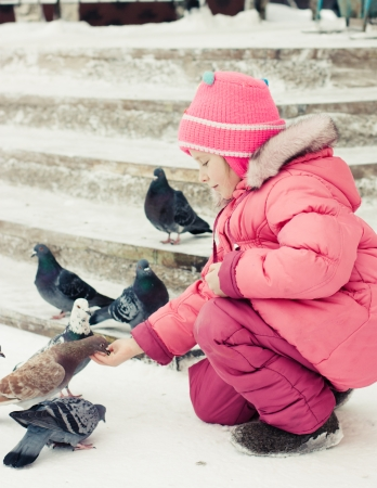 Child feeding doves in the city street winter  photo
