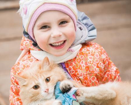 enfermera con cofia: Happy child in warm clothes with a kitten.