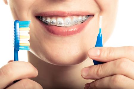 dientes: Bella joven sonriente con retenedor para los dientes cepillarse los dientes sobre un fondo blanco.