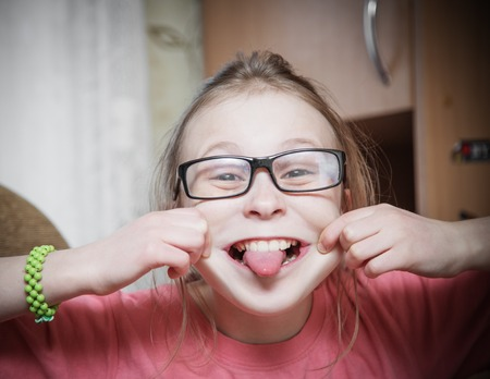 teases: Funny girl in a glasses showing tongue.