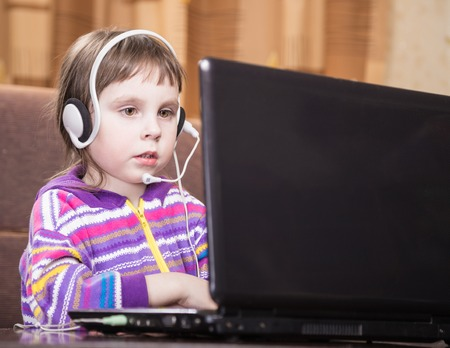 internet safety: Girl Using a Laptop in the room.