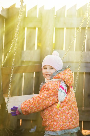 playpen: Kid swinging on a swing in the yard. Stock Photo