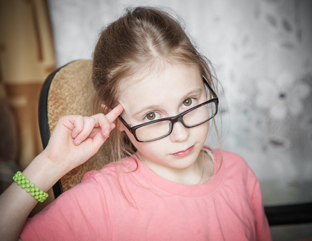 teases: Funny girl in glasses showing spinning finger to his temple. Stock Photo