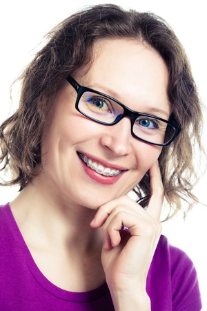 crooked teeth: Beautiful smiling girl wearing braces on a white background. Stock Photo