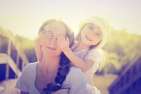 little: Daughter hugging mother on the a nature.