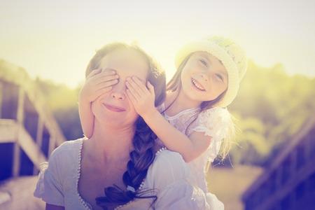 jolie petite fille: Fille étreignant mère sur la nature.
