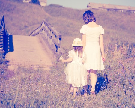 cross street with care: Mother and daughter walking on the sunny meadow. Stock Photo