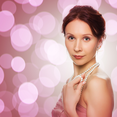 pink pearl: Beautiful woman with pearl beads on a pink background. Stock Photo