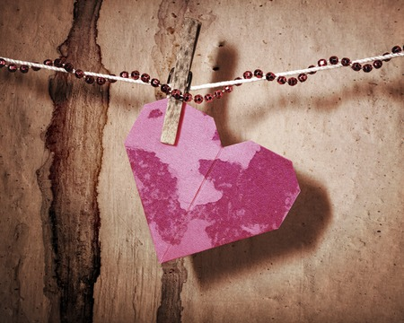 love hurts: Broken red heart hung on rope, in grunge style.