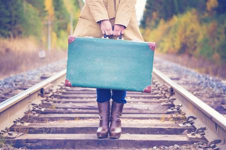 Mujer elegante con una maleta que viaja por día de otoño ferroviario. Foto de archivo