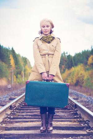 maleta: Mujer elegante con una maleta que viaja por día de otoño ferroviario.