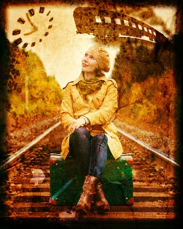 Elegant woman with a suitcase waiting for a train. Photos in the grunge style. Imagens