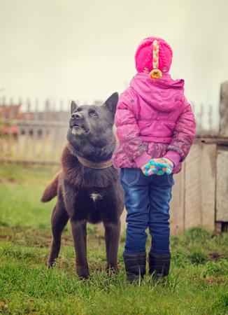 Perro enojado mira a un niño sin miedo. Foto de archivo