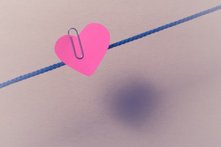 Red paper heart hitched to clip to the rope. Stock Photo