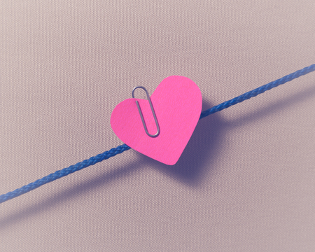 hitched: Red paper heart hitched to clip to the rope. Stock Photo