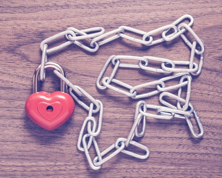 door lock love: Lock heart with chain on a wooden surface.