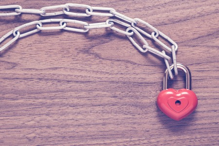 bibelot: Lock heart with chain on a wooden surface.