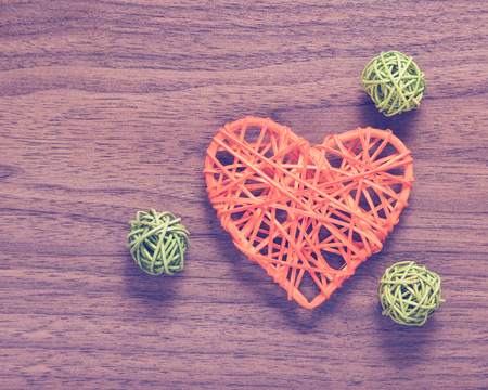 reciprocity: Wicker heart handmade with lying on a wooden background. Stock Photo