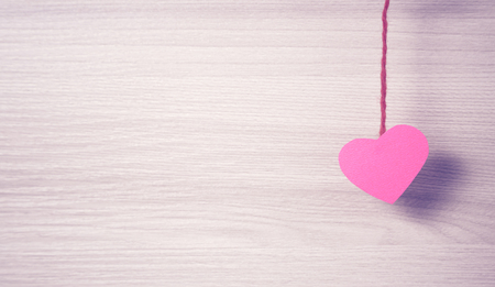 hitched: Red paper heart hitched to the rope. Stock Photo
