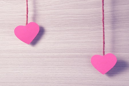 string together: Two paper hearts hanging on a rope. Valentines day theme. Stock Photo