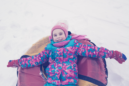 winter photos: Cute kid riding snow tube winter day. Photos in retro style.
