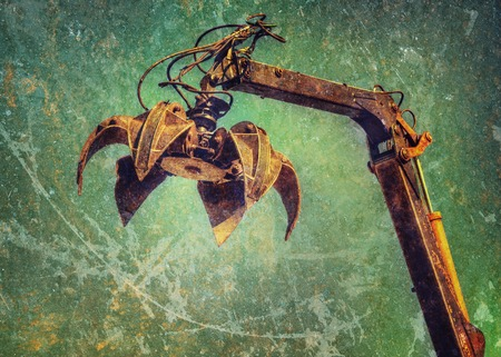 grabber: Crane claw on up in recycling center. Photos in a grunge style.