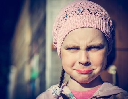 doleful: Close-up portrait of sad little girl with pursed lips. Photos in retro style.