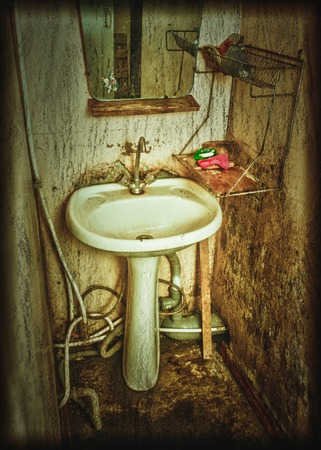 seep: Old rusty wash basin on the dirty tile. Stock Photo
