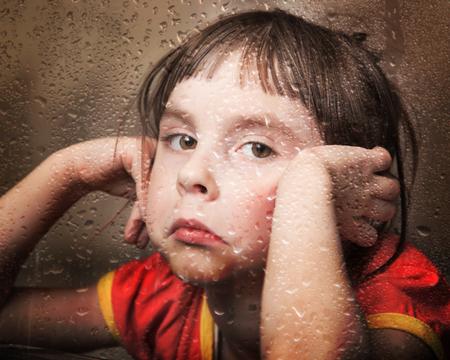 persona triste: Kid triste en tiempo de lluvia en la ventana.
