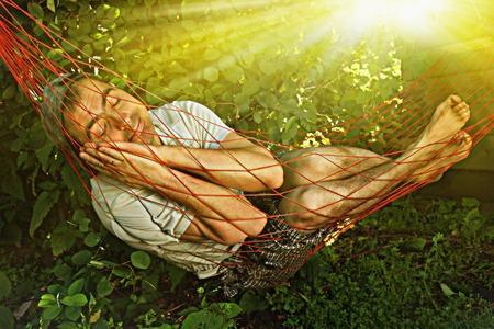 Lustiger Mann barfuß in einer Hängematte unter der Morgensonne schlafen.