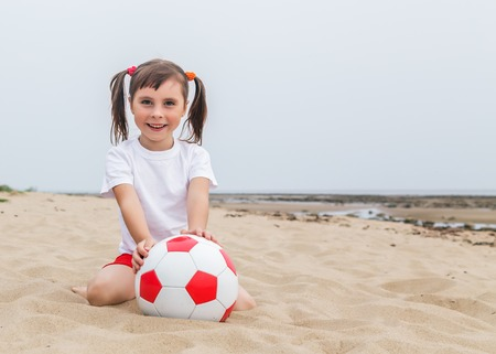 Little girl with pigtails sitting on the sand to catch a soccer ball.