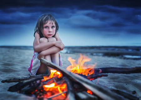 hugging knees: Desperate child hugging her knees with tears in his eyes, night sitting on the beach campfire. Stock Photo